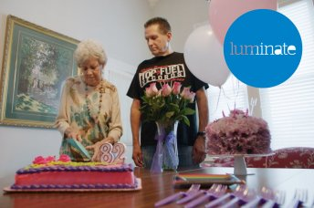 A man standing with an older lady and a birthday cake