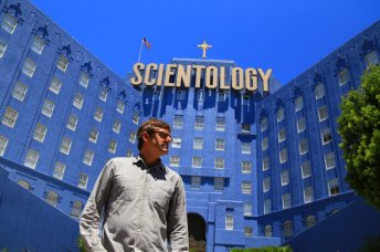 Man standing in front of large church with words above it saying scientology