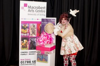Panto dame putting massive coin in collection box